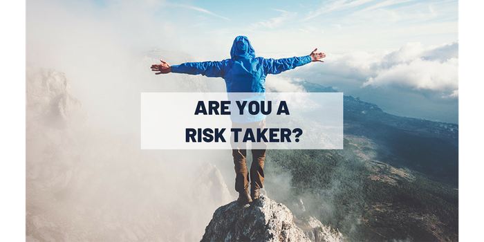 "Person standing on edge of a cliff with ""are you a risk taker?"" on top of photo"