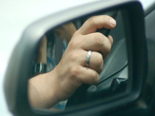 Person's hands on car steeling wheel from the view of the side mirror