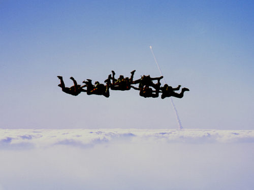 Group of people skydiving and holding hands in midair