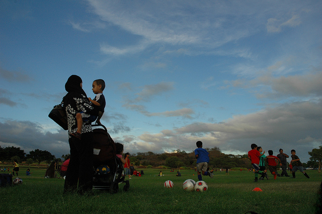 Mom holding kid watching kids playing a soccer game