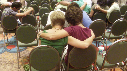 Two people sitting down hugging eachother