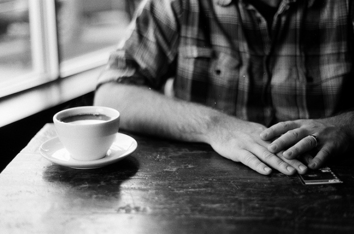 Person sitting at table with a cup of coffee in front of them