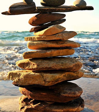 Rocks balancing on top of each other on ledge in front of the ocean