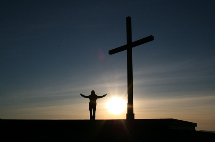 Person standing on roof with cross and sun setting in the back