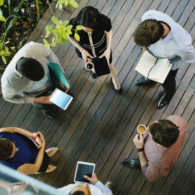 Group of people standing in a circle holding coffee, notebooks, tablets