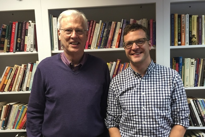 Two men standing next to each other in front of a bookcase